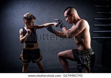 Kickboxing coach is training the boy. The concept of family, sports, mma, muay thai. Mixed media Royalty-Free Stock Photo #1674481741