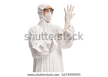 Man in a white decontamination suit putting on medical gloves isolated on white background Royalty-Free Stock Photo #1674490495