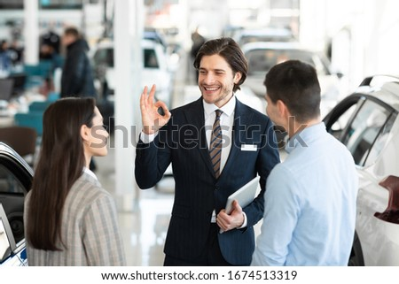 Professional Car Dealer Gesturing Okay Talking With Clients Offering Great Deal Working In Auto Dealership Store #1674513319