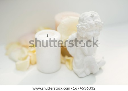 Statuette of an angel, a candle and rose petals on the table. #1674536332