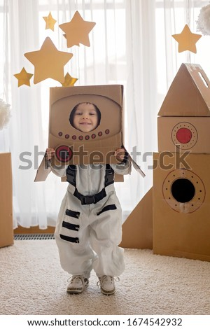 Sweet toddler boy, dressed as an astronaut, playing at home with cardboard rocket and handmade helmet from box Royalty-Free Stock Photo #1674542932
