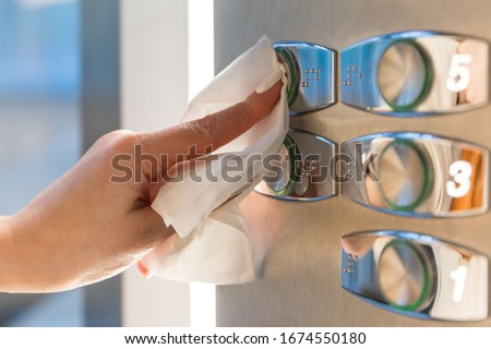 Close up of woman forefinger pressing the button in the elevator through a napkin, to protect yourself from contact with viruses, germs during a coronavirus pandemic, covid-19. Quarantine concept Royalty-Free Stock Photo #1674550180