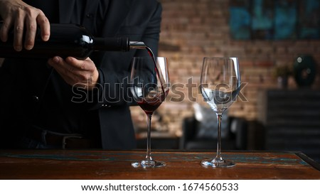 Elegant man pouring red wine from wine bottle to wine glasses at home in a cosy dark room. #1674560533