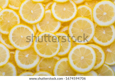 Yellow sliced lemons places on a table overlapping each other. Background texture of fresh yellow fruit.  #1674594706