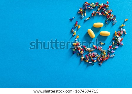 Concept of herd immunity. Group of miniature people with yellow pills on light blue background, get sick and become immune to viruses. Spread of virus treatment through a vaccine. Herd immunity viral Royalty-Free Stock Photo #1674594715