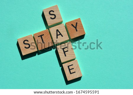 Stay Safe, words in 3d wood alphabet letters in crossword form isolated on blue background Royalty-Free Stock Photo #1674595591