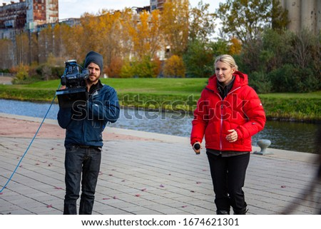 Montreal, Quebec / Canada - October 16 2010: Reporter Wearing a Red Clothes is Holding a Microphone in her Hand for Recording a TV News Story in front of a Cameraman with his Panasonic Shoulder Camera #1674621301