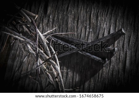 Black and white image of crown of thorns and nails again vintage wooden background as symbol of crucifixion of Jesus Christ.
