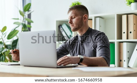 Side view of concentrated at work confident young man in glasses in smart casual wear working on laptop while sitting near window at home. Hard process of education, social distancing #1674660958
