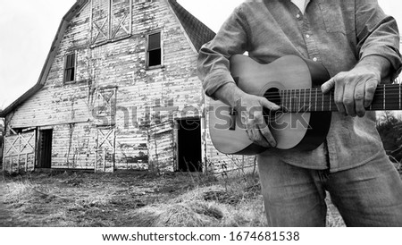 closeup of man holding acoustic guitar standing in front of old abandoned barn on farm in country, cannot see man's face, black and white photo