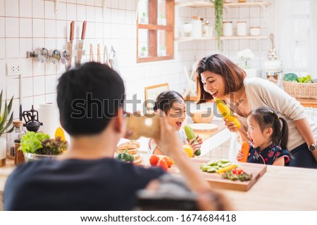 Asian family enjoy playing and cooking food in kitchen at home #1674684418