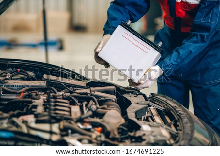 Male mechanic changing car battery, engineer is replacing car battery because car battery is depleted. concept car maintenance #1674691225