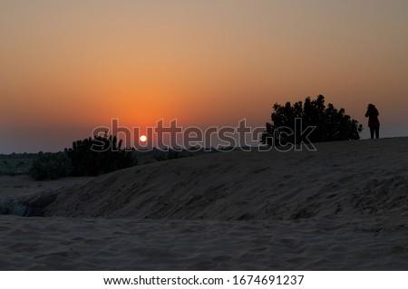 Female tourist taking picture of Sunrise at Thar desert, Rajasthan India with desert plants in frame.