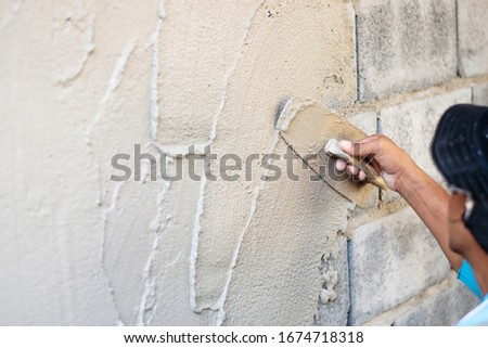Close-up of the hands of the workers plastering, building the house wall. #1674718318