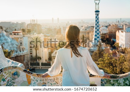 Young female tourist spending vacation in Barcelona,Catalonia,Spain.Traveling to Europe,visiting Parc Guell UNESCO site famous historical landmarks.Panoramic view on entrance.Best sunrise in Barcelona #1674720652