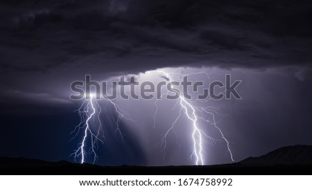 Lightning bolt strike from a thunderstorm with rain and dramatic storm clouds Royalty-Free Stock Photo #1674758992