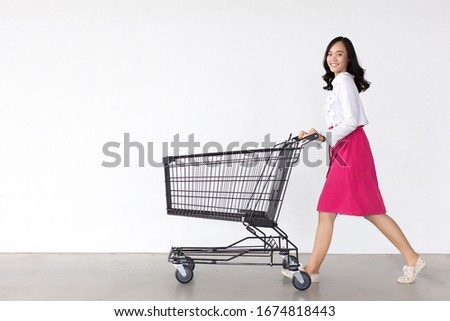 happy asian woman with shopping cart trolley in sale season. Shopaholic concept. #1674818443