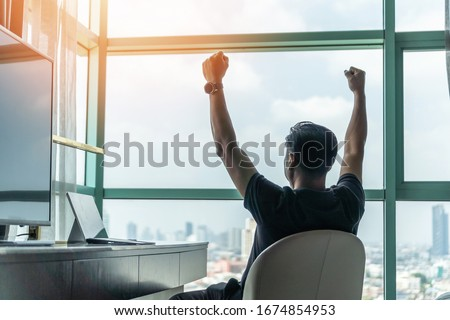 Business achievement concept with happy businessman relaxing in office or hotel room, resting and raising fists with ambition looking forward to city building urban scene through glass window #1674854953