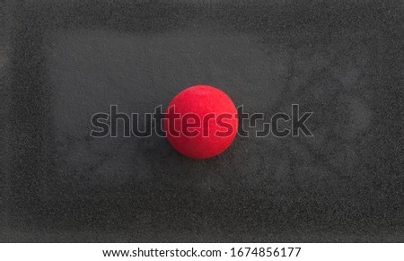 red clown nose on a black background