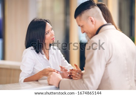 female receptionist at counter in hotel with Young couple receiving tourist information