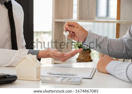 Real estate agent broker hand over the house key to the new owner after completing the signing according to agreement renting a house and buy house insurance Home insurance concept.