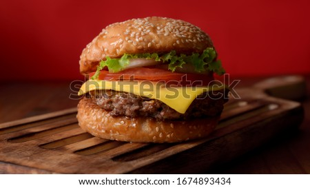 Close up view of Fresh tasty beef burger on wooden tray on rustic table white red wall background #1674893434