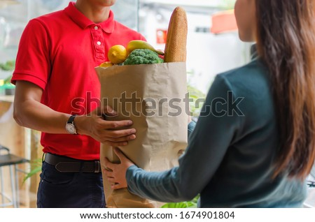 smart food delivery service man in red uniform handing fresh food to recipient and young woman customer receiving order from courier at home, express delivery, food delivery, online shopping concept #1674901804