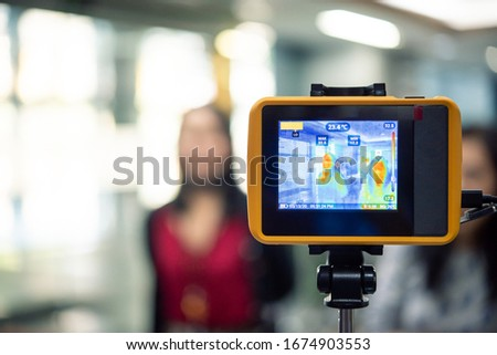 Asian people waiting for body temperature check before access to building for against epidemic flu covid19 or corona virus from wuhan in office by thermoscan or infrared thermal camera #1674903553