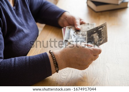Memory. Eldery woman looking vintage photos.