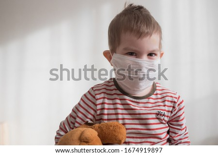 Toddler boy in medical mask embracing his teddy bear. Home isolation coronavirus covid-2019 quarantine #1674919897