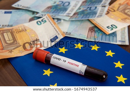 euro banknotes and europe flag with corona virus blood test tube #1674943537