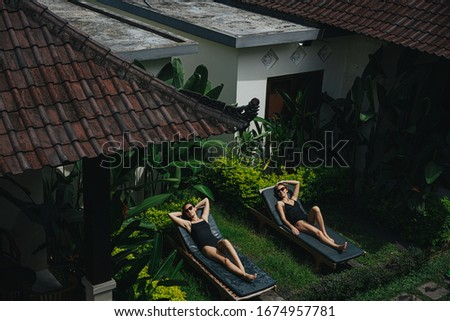 Two girlfriends in the garden of an Asian hotel, relaxing while sunbathing. View from above #1674957781