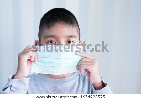 Portrait Asian kid wearing medical mask.A boy wearing mouth mask against air smog pollution. Concept of corona virus quarantine or covid-19.Protection against virus and infection control concept. #1674998575