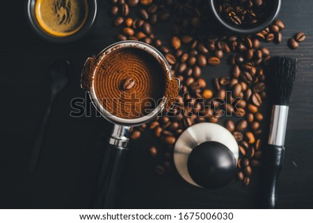 High angle view of espresso, porta filter, coffee beans, ground coffee, brush and tamper #1675006030