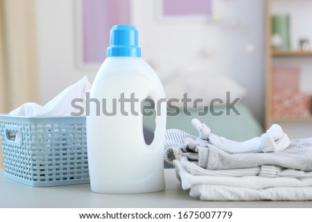 Baby clothes and detergents on the table. Baby clothes care concept. #1675007779
