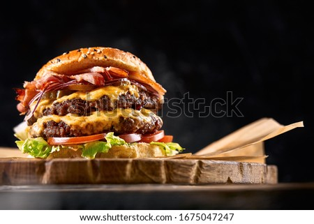 Juicy burger on the board, black background. Dark background, fast food. Traditional american food. Copy space. Royalty-Free Stock Photo #1675047247