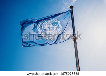 UN flag waved against the sun and blue sky. Royalty-Free Stock Photo #1675095586