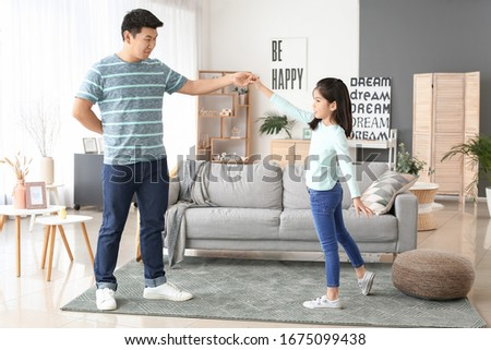Happy Asian man and his little daughter dancing at home #1675099438