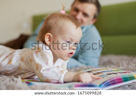 baby reads a picture book. Learn animal colors. Training and game early development. Home leisure with a small child. Family young home coziness. Parenting