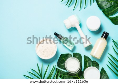 Beauty product. Face massage brush, hyaluronic acid, cream for face, clay mask on blue background. Skin care concept. Flat lay image with copy space. Royalty-Free Stock Photo #1675111636
