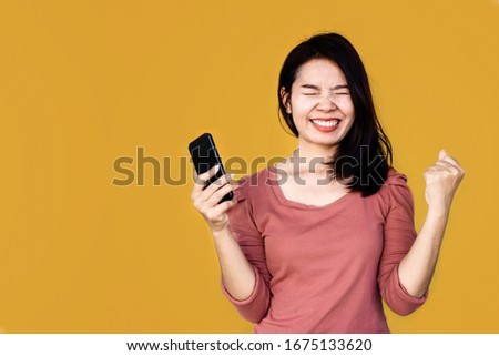 cheerful happy Asian woman get good news hand holding smart phone over yellow background   #1675133620
