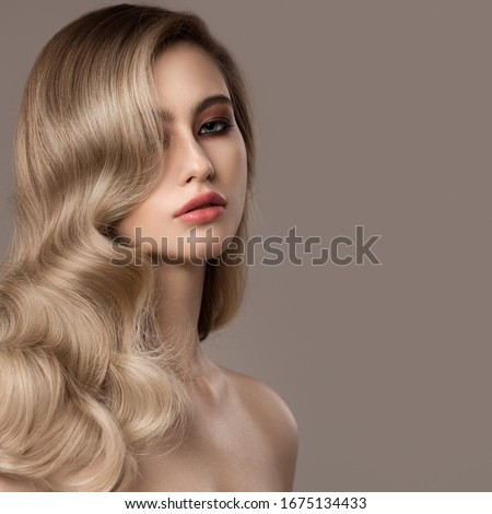 Portrait of young blonde woman. Long beautiful wavy hair. Royalty-Free Stock Photo #1675134433