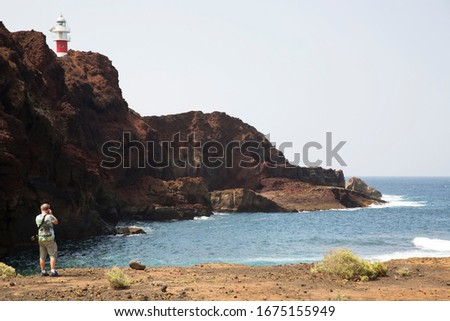 tourists making pictures of the old lava flow coast and the lighthouse of Punta de Teno, Tenerife