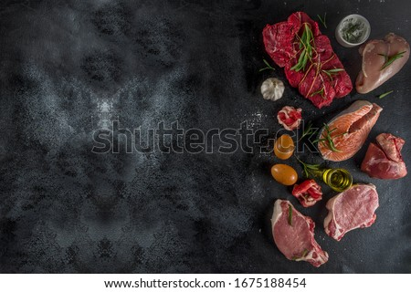 Carnivore diet background. Non vegan protein sources, Different meat food - chicken breast, pork steak, beef tenderloin, eggs, spices for cooking. Black stone concrete background copy space Royalty-Free Stock Photo #1675188454
