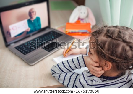 Pretty stylish schoolgirl studying homework math during her online lesson at home, social distance during quarantine, self-isolation, online education concept, home schooler #1675198060