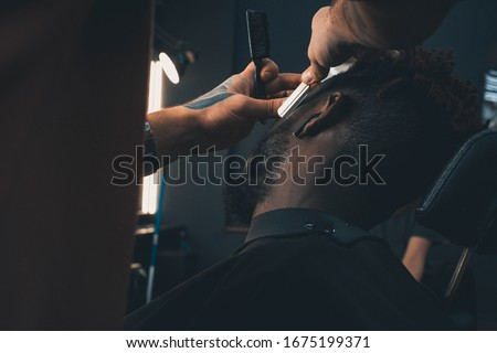 Young African-american man visiting barbershop. Brings a beard in order with the help of a hairdresser.  Self-care, masculine beauty.  Black African Hair Trimmer. #1675199371