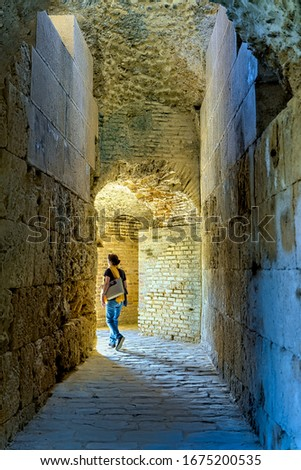 Santiponce, Spain. Circa March 2020. Woman walks along stone corridor in the Roman city of Italica in Santiponce, Spain. #1675200535