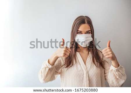 Woman suffer from sick and wearing face mask. Girl, young woman in protective sterile medical mask on her face looking at camera an showing thumb up sign.  Copy-space in left part of image. #1675203880