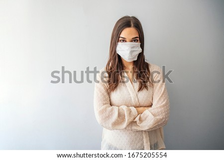 Beautiful young woman in white t-shirt with disposable face mask. Protection versus viruses and infection. Studio portrait, concept with gray background. Woman suffer from sick and wearing face mask. #1675205554