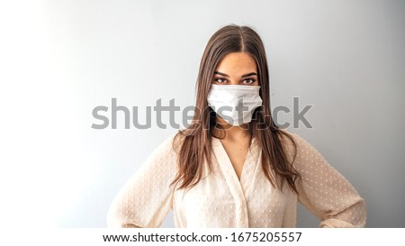 Girl in respiratory mask. Masked woman looks at camera. Cold, flu, virus, tonsillitis, respiratory disease, quarantine, epidemic concept. Beautiful caucasian young woman with disposable face mask Royalty-Free Stock Photo #1675205557